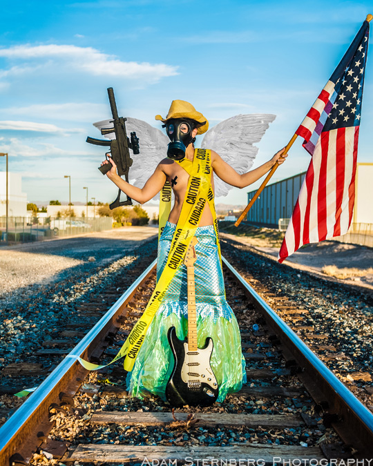 Every Photographic Cliche rolled into one photo. Here Sarah Jane Woodall poses topless with electrical tape pasties on railroad tracks while wearing a cowboy hat, mermaid outfit, angel wings, and a gas mask while holding a machine gun and American flag while posing with an electric guitar...the whole enchilada!