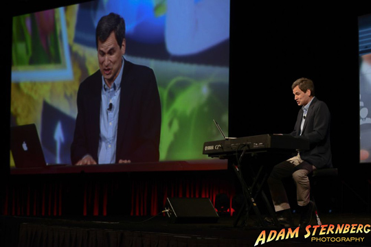 A wider shot of David Pogue on stage. This time with a photo of the live video of his performance behind him.